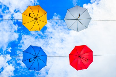 four assorted-color umbrellas hanged on cable under cloudy sky bright zoom background