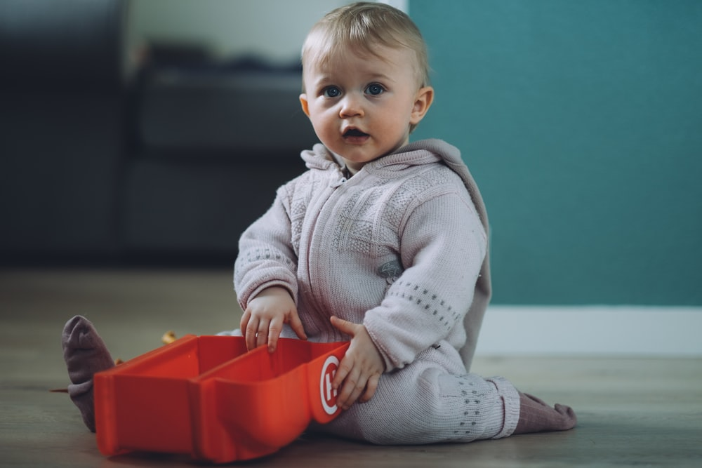 toddler sitting on ground while holding red plastic case