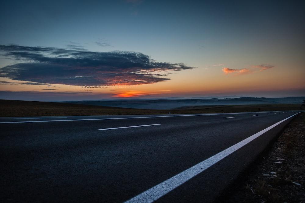 black concrete road during sunset