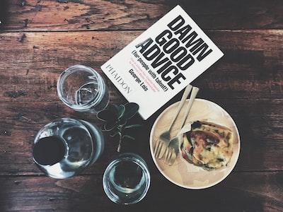 木のテーブルの上のアドバイス本と食事
