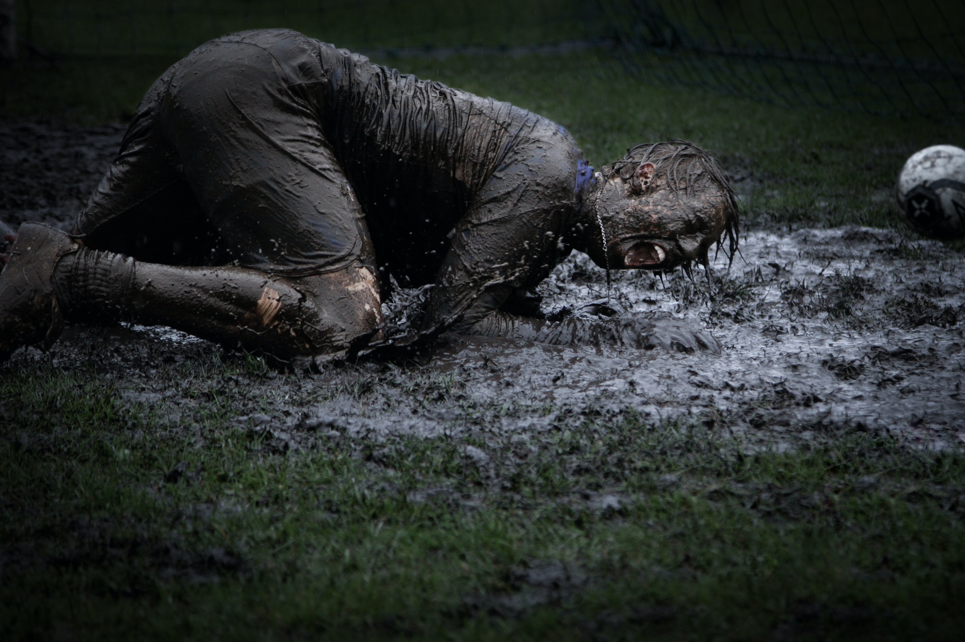 man lying on green grass soaked with mud
