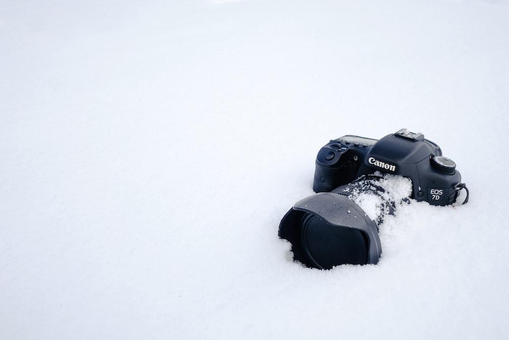 black Canon DSLR camera on snow field