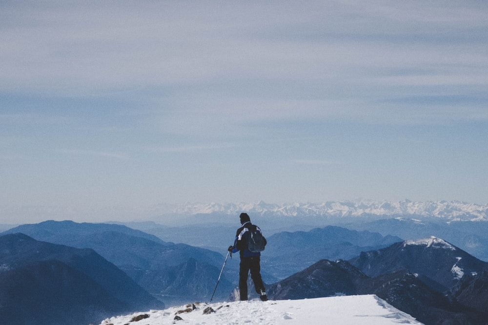 person standing black backpack standing on peak at daytime