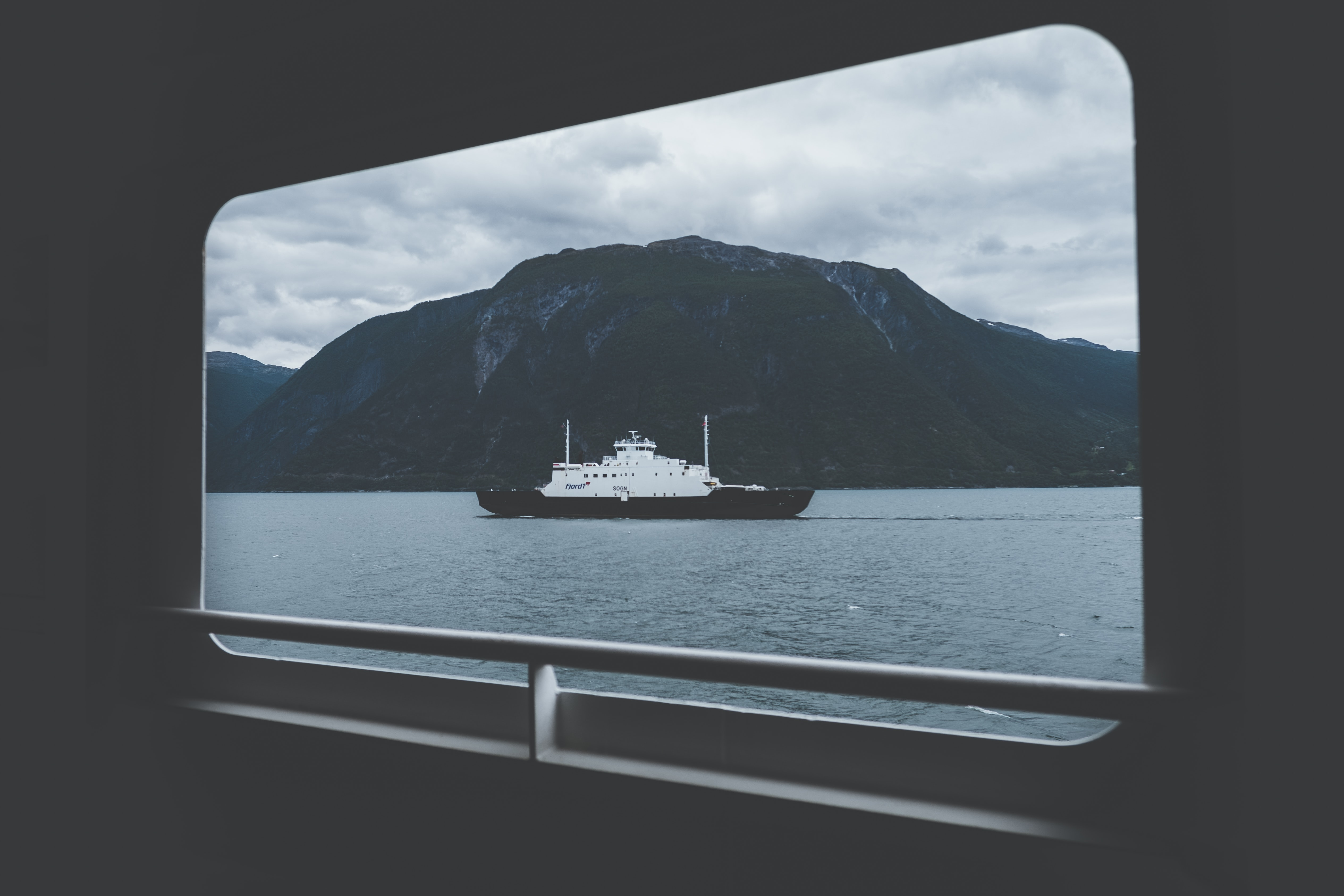 ship on body of water under gray sky during daytime