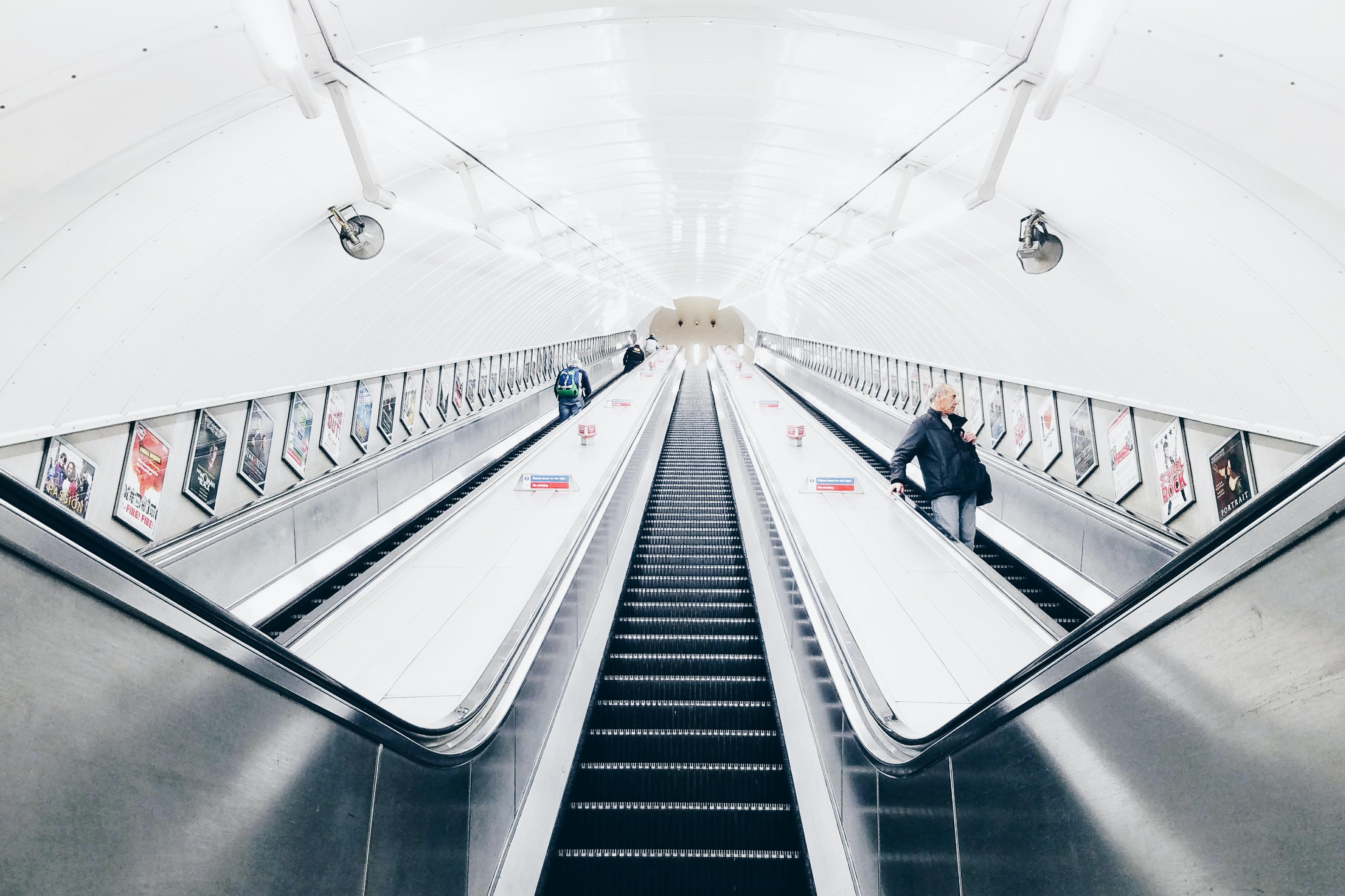 people riding escalator inside white room