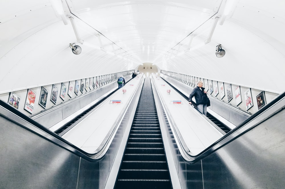 people riding escalator inside white room
