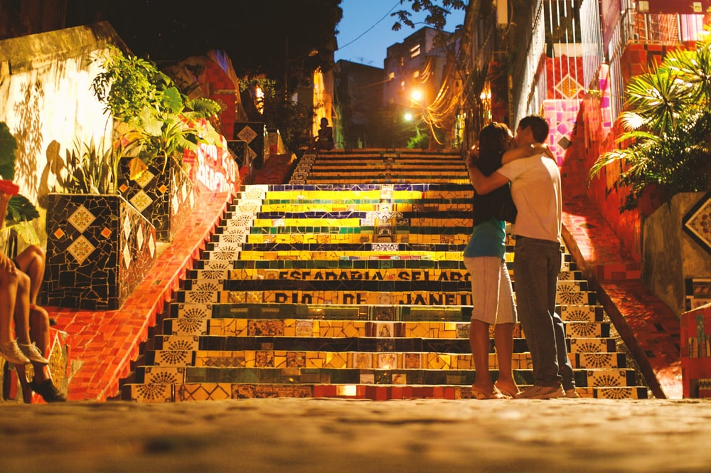 man and woman kissing in front of stairs