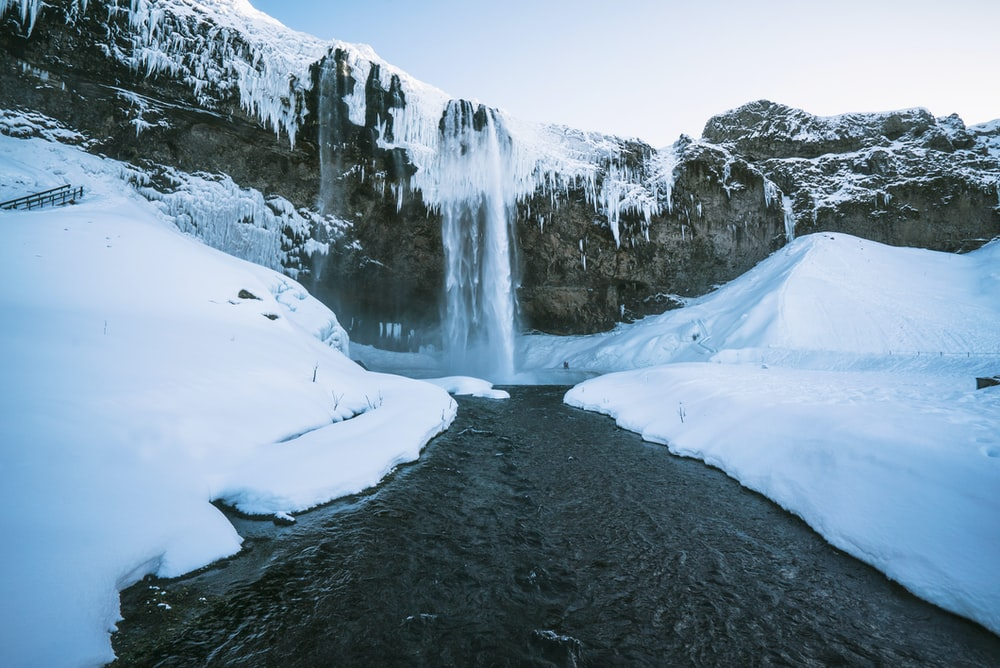 waterfalls flowing down between snows