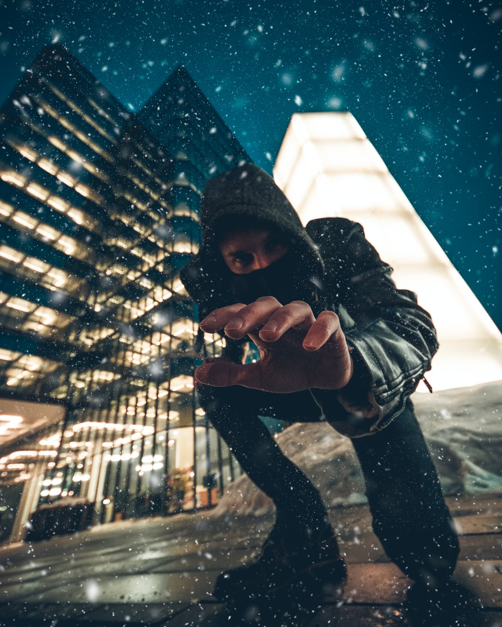 close-up photography of man kneeling on ground front of gray high-rise building during snow weather