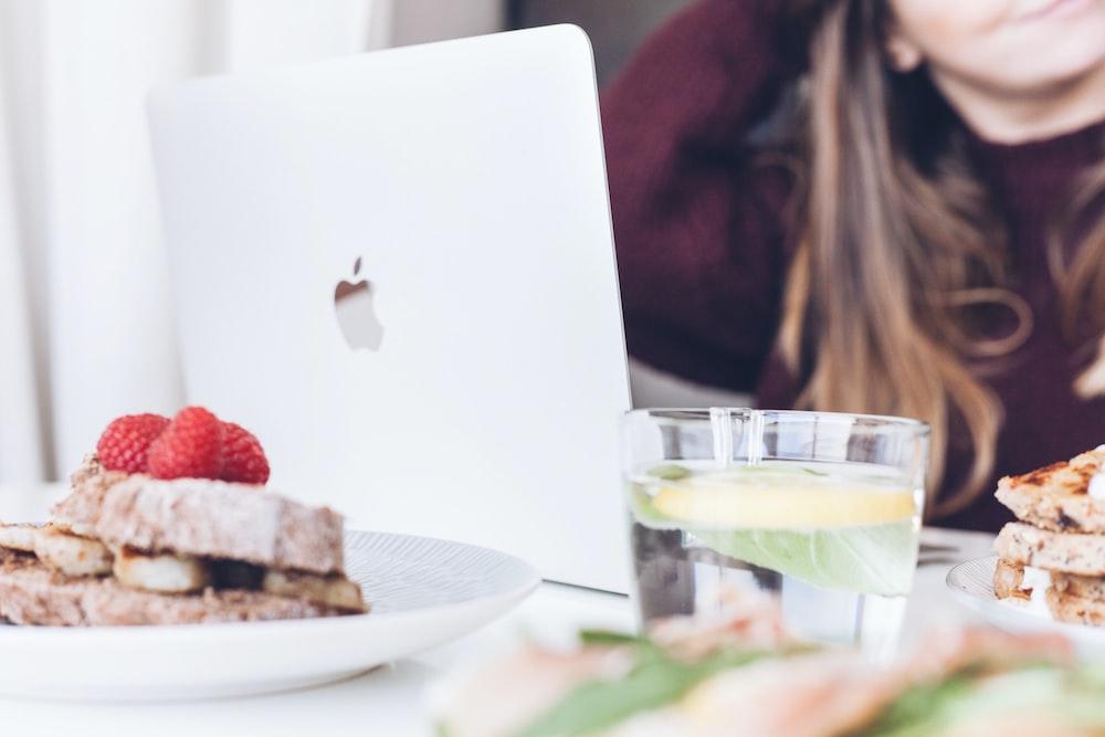 clear drinking glass near silver MacBook
