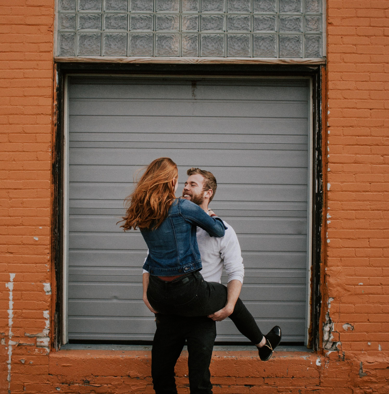 man carrying woman near shutter door