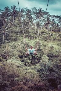 woman sitting on swing facing trees