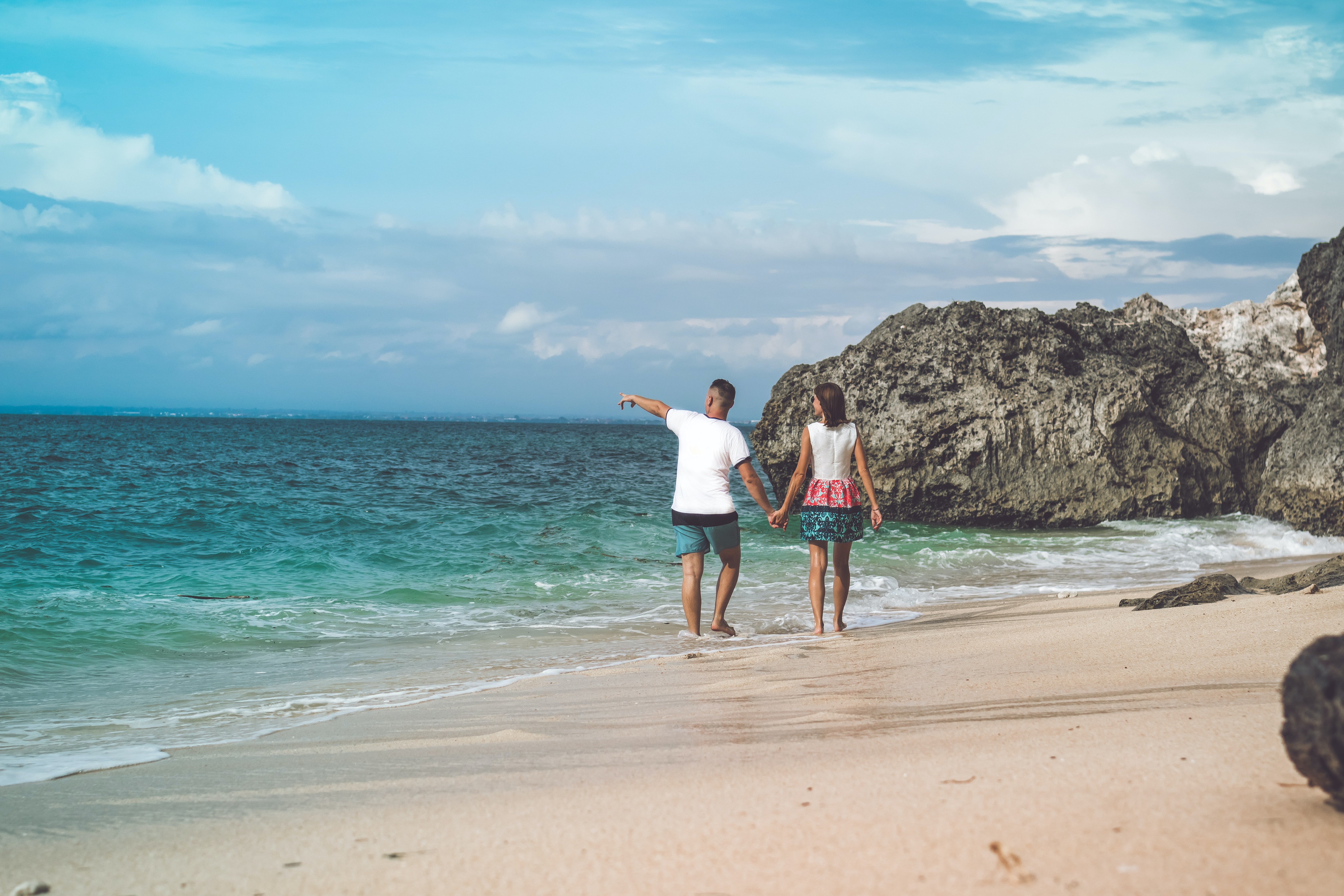 man and woman walking on seashore while holding hands during daytime