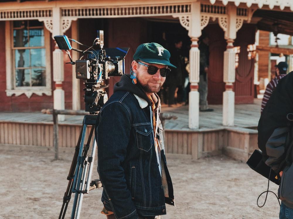 man in jacket beside camera