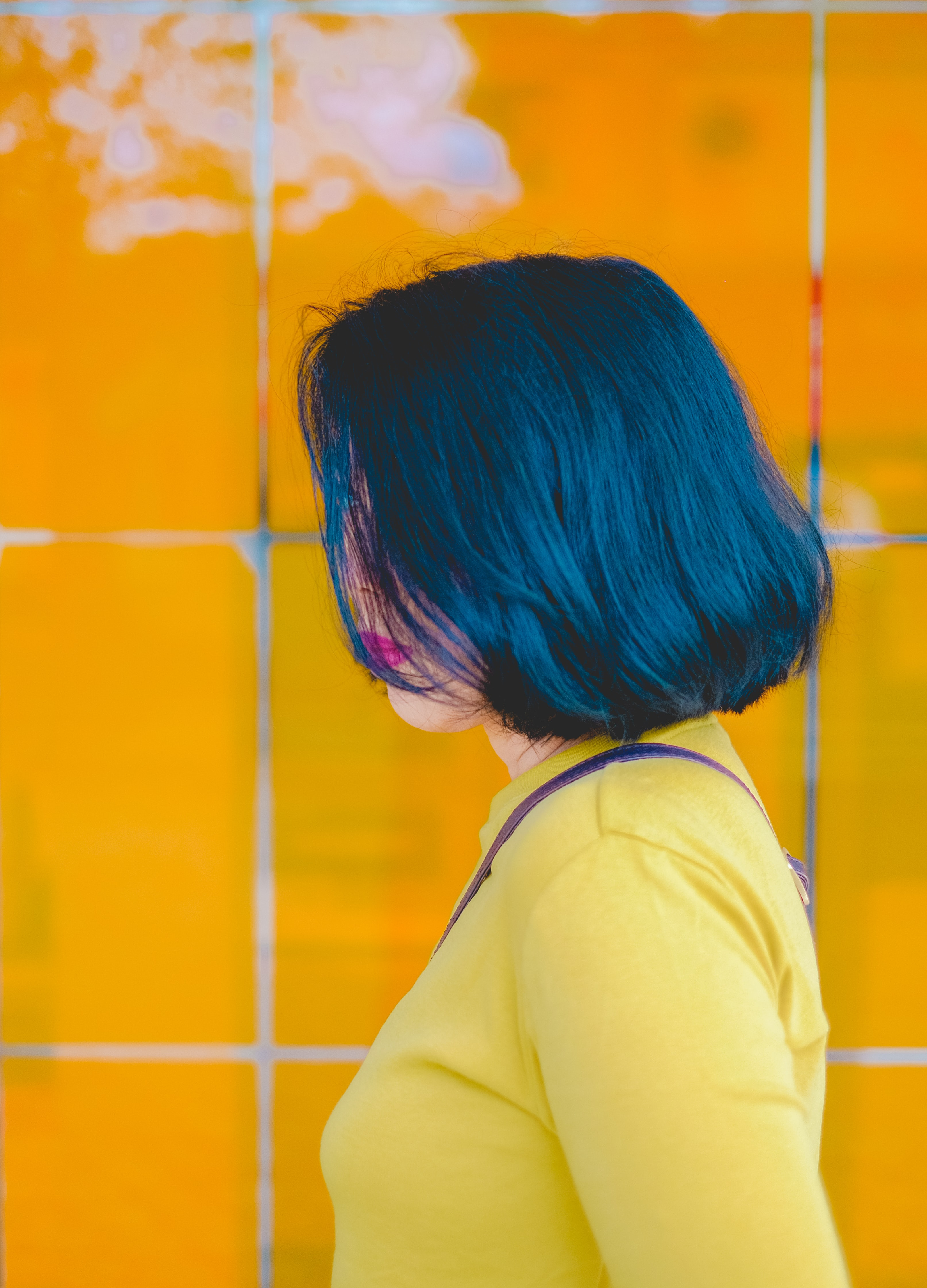 black haired woman in yellow long-sleeved top