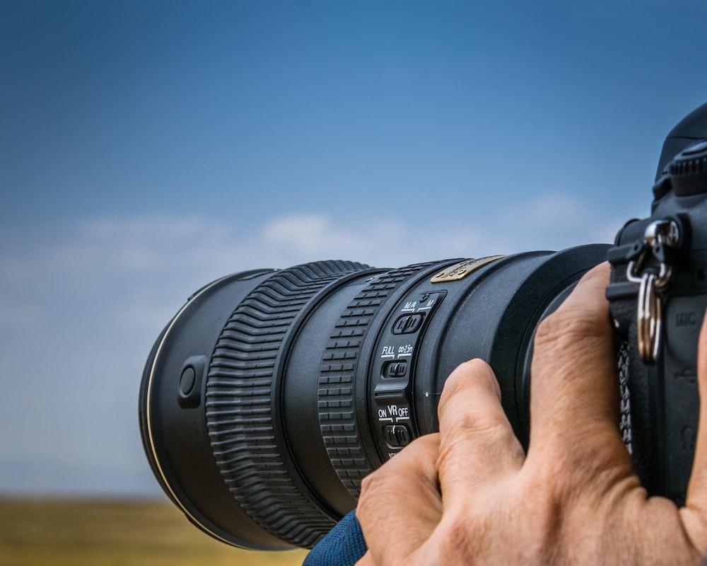 黒のデジタル一眼レフカメラを使用している人