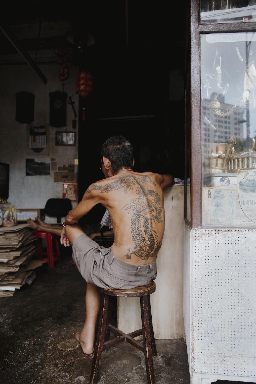 man sitting on wooden stool