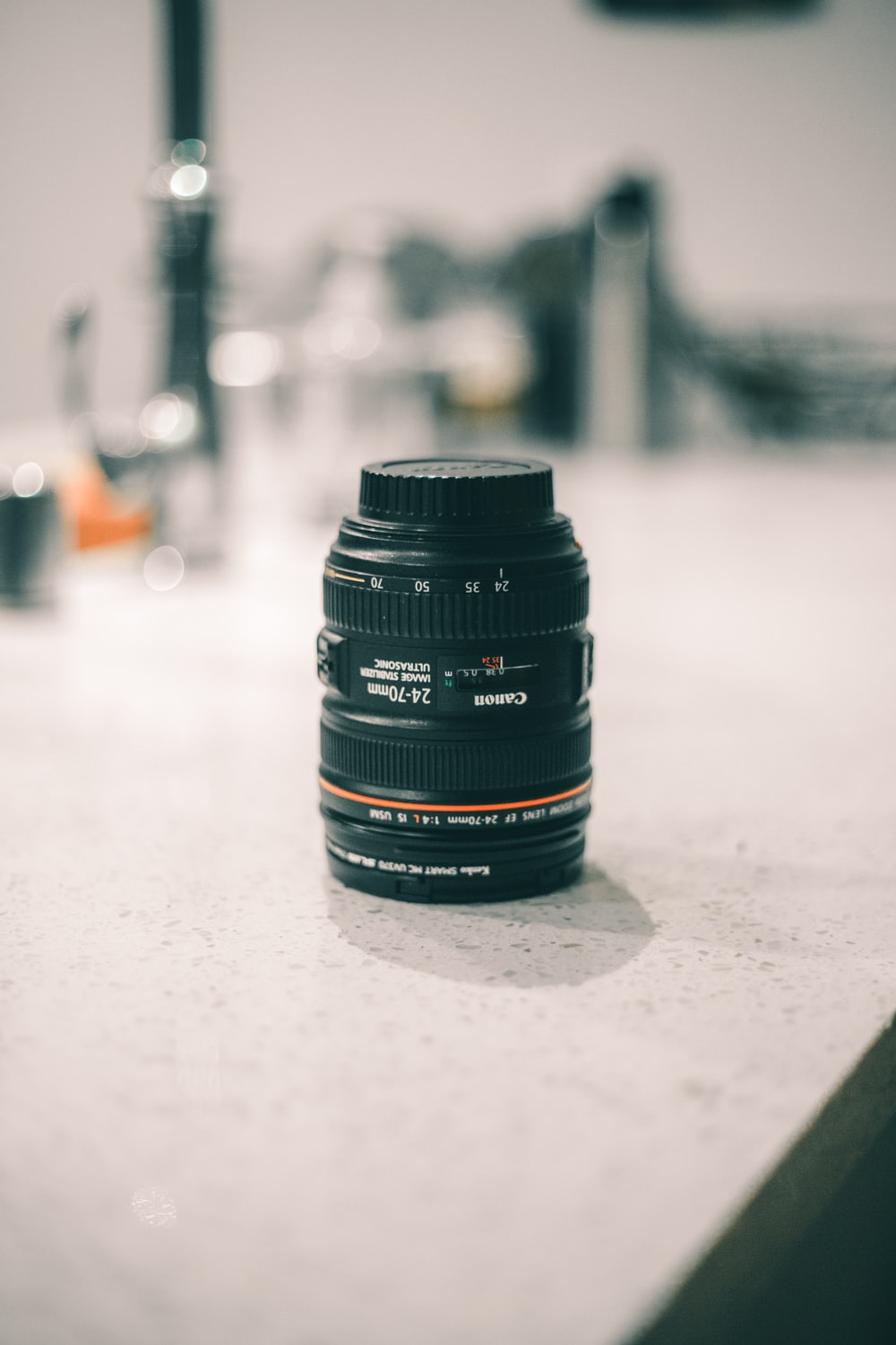 shallow focus photography of camera lens on top of counter