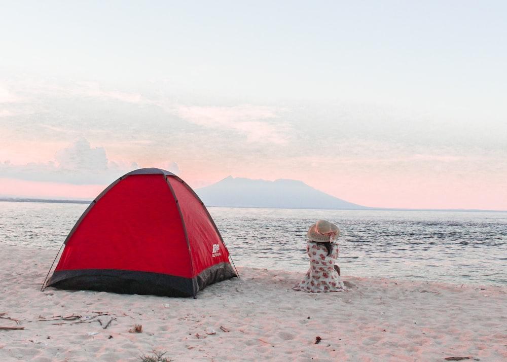 red and black dome tent near seashore