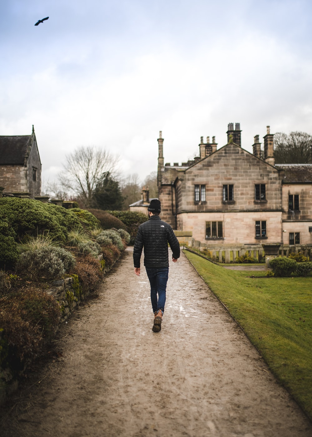 man walking on dirt road near brick house during daytime