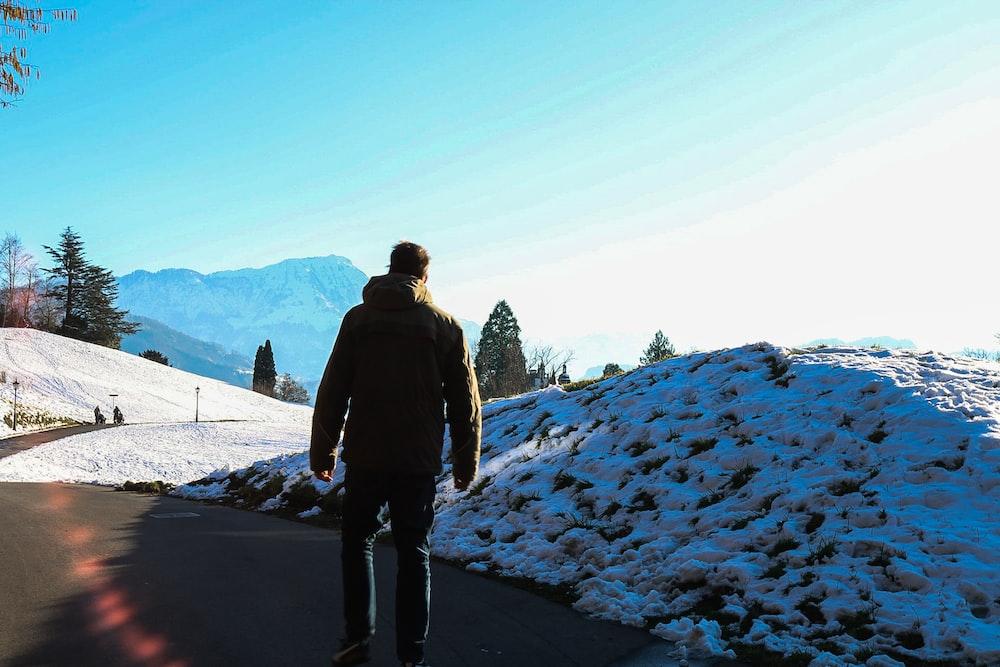 man standing near snow pile