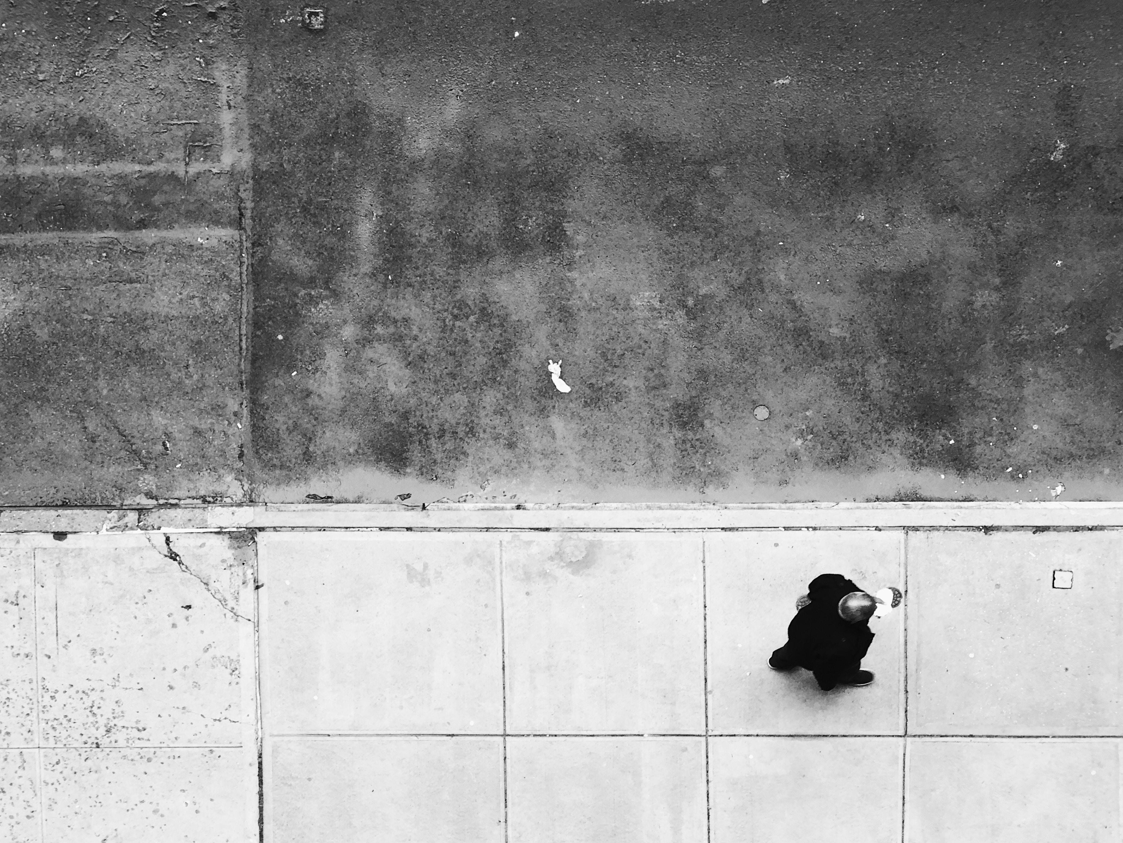 man walking on tiled pathway