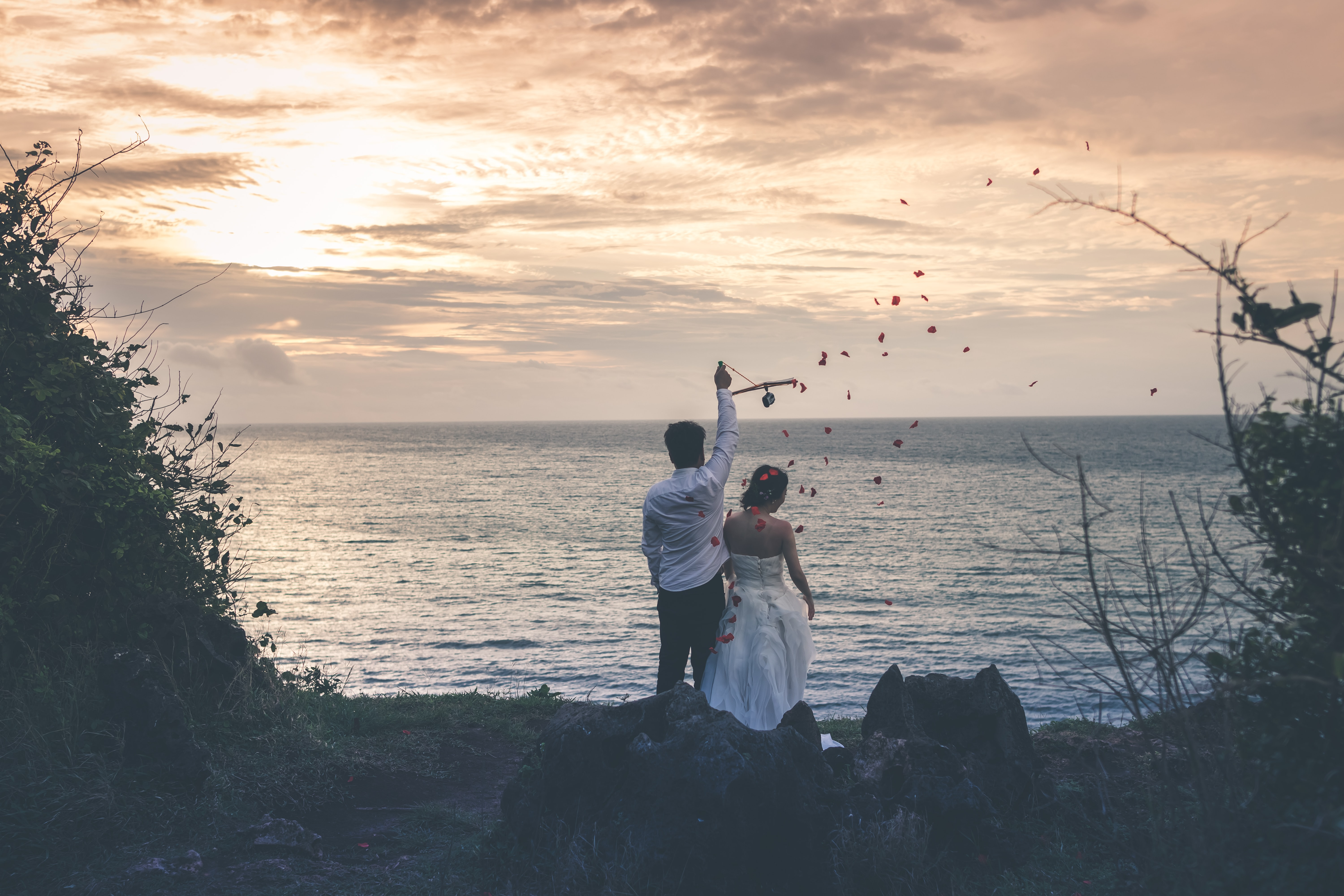 bride and groom standing in front of water body