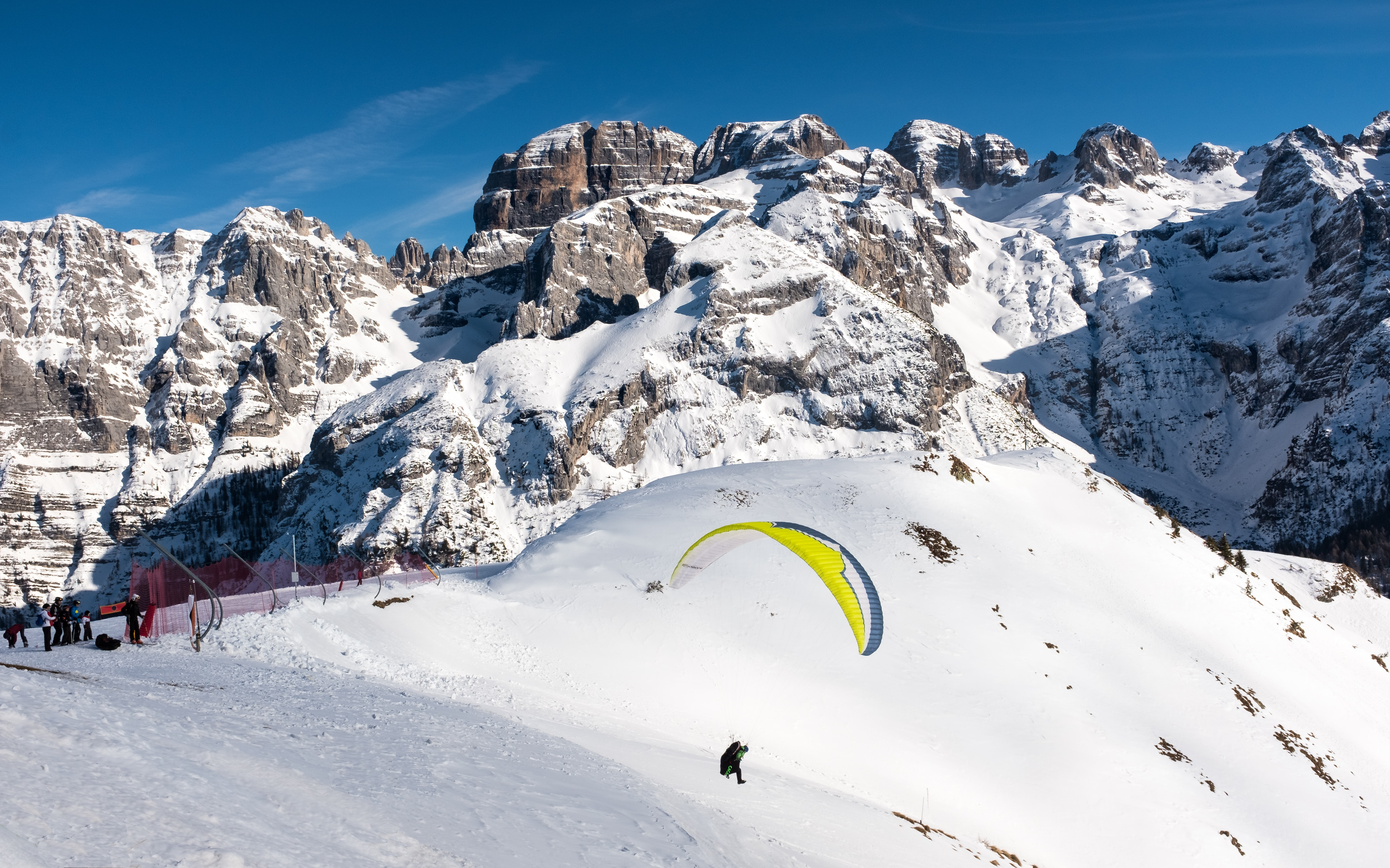person paragliding above mountain with snow