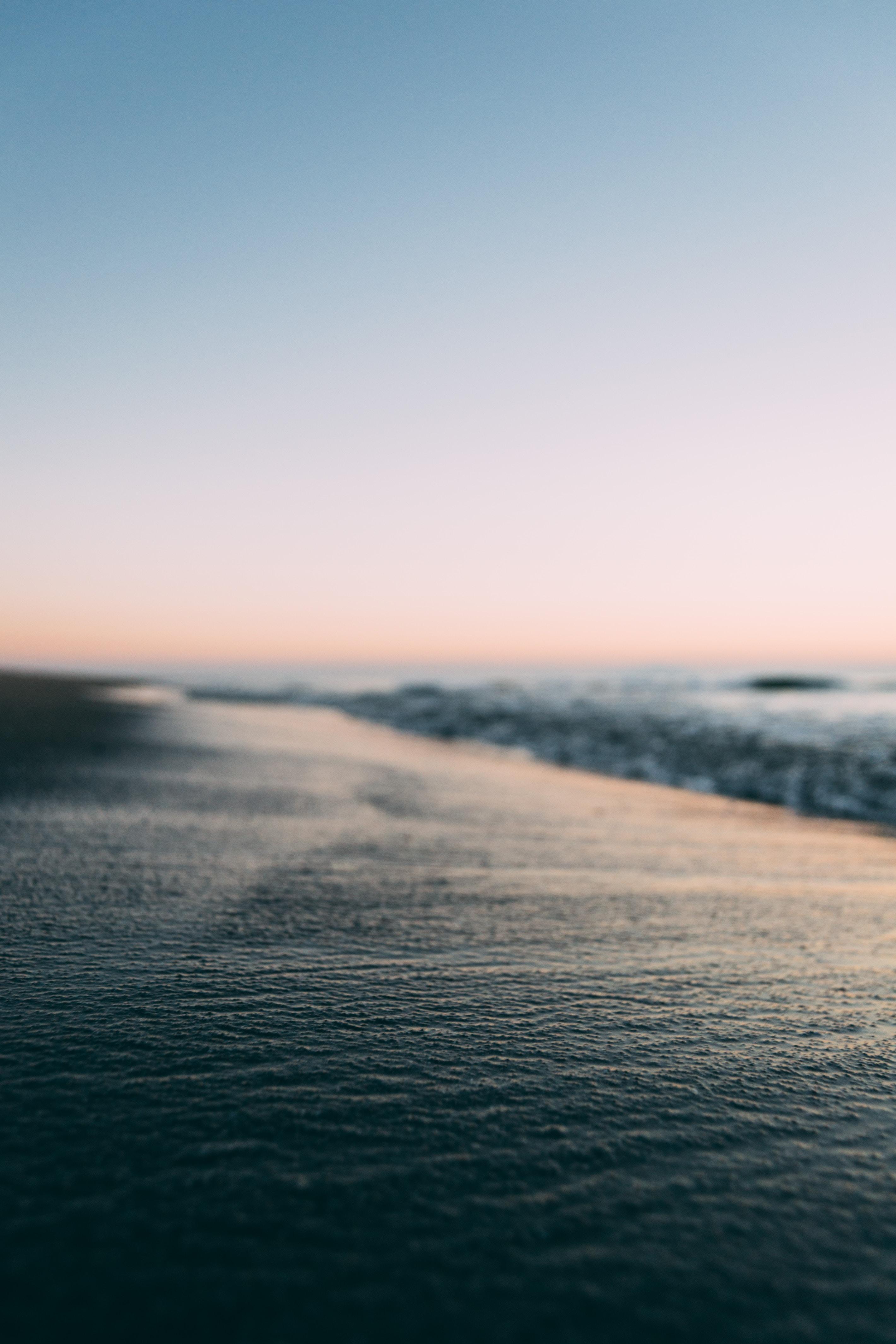 selective focus photography of black beach sand