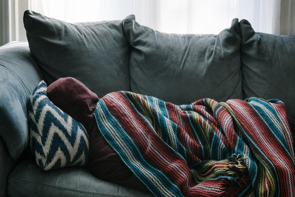 person lying on gray sofa