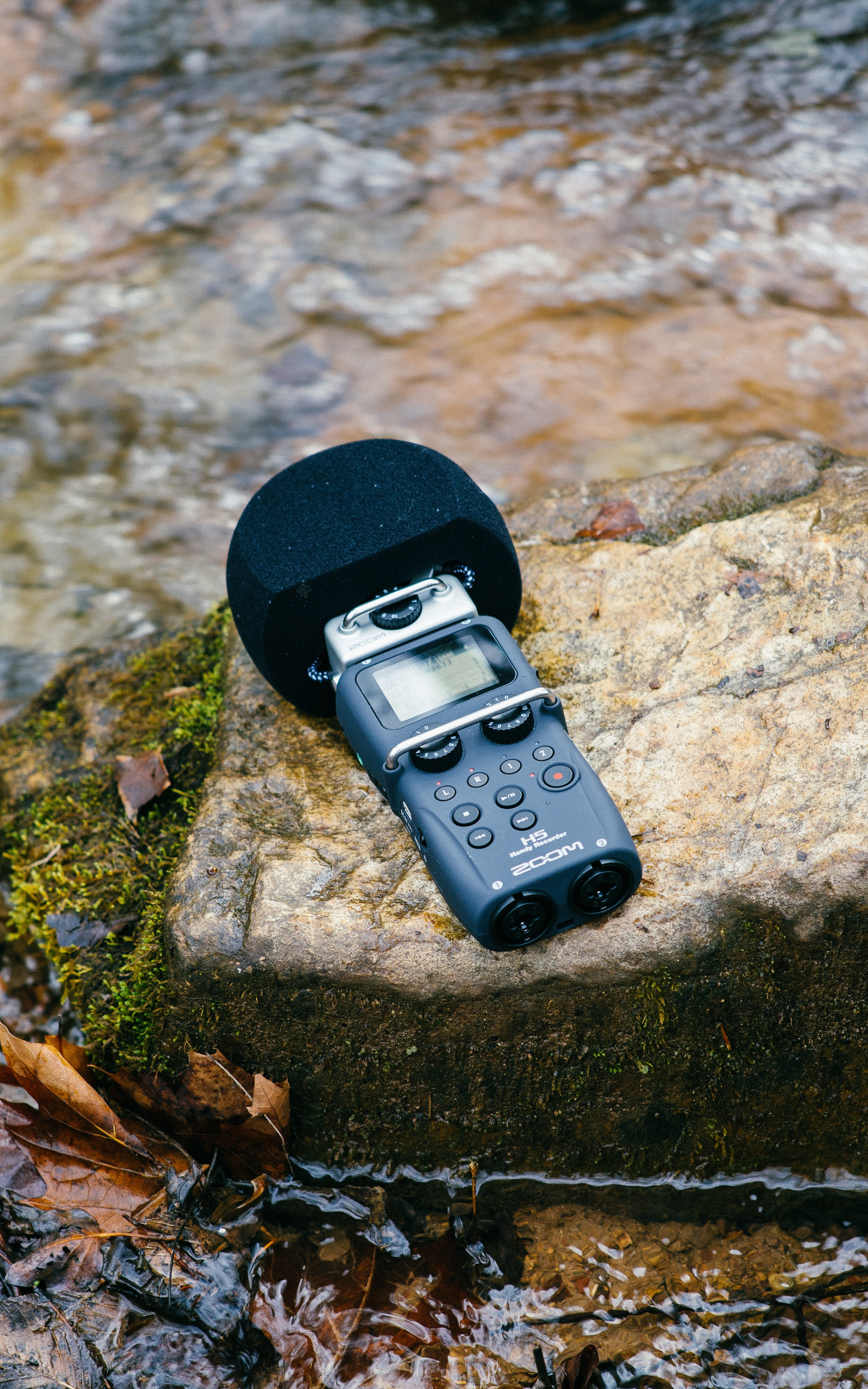 black digital wireless microphone on mossy rock