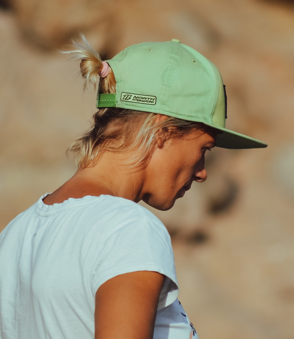 tilt-shift photography of woman with green fitted cap at daytime