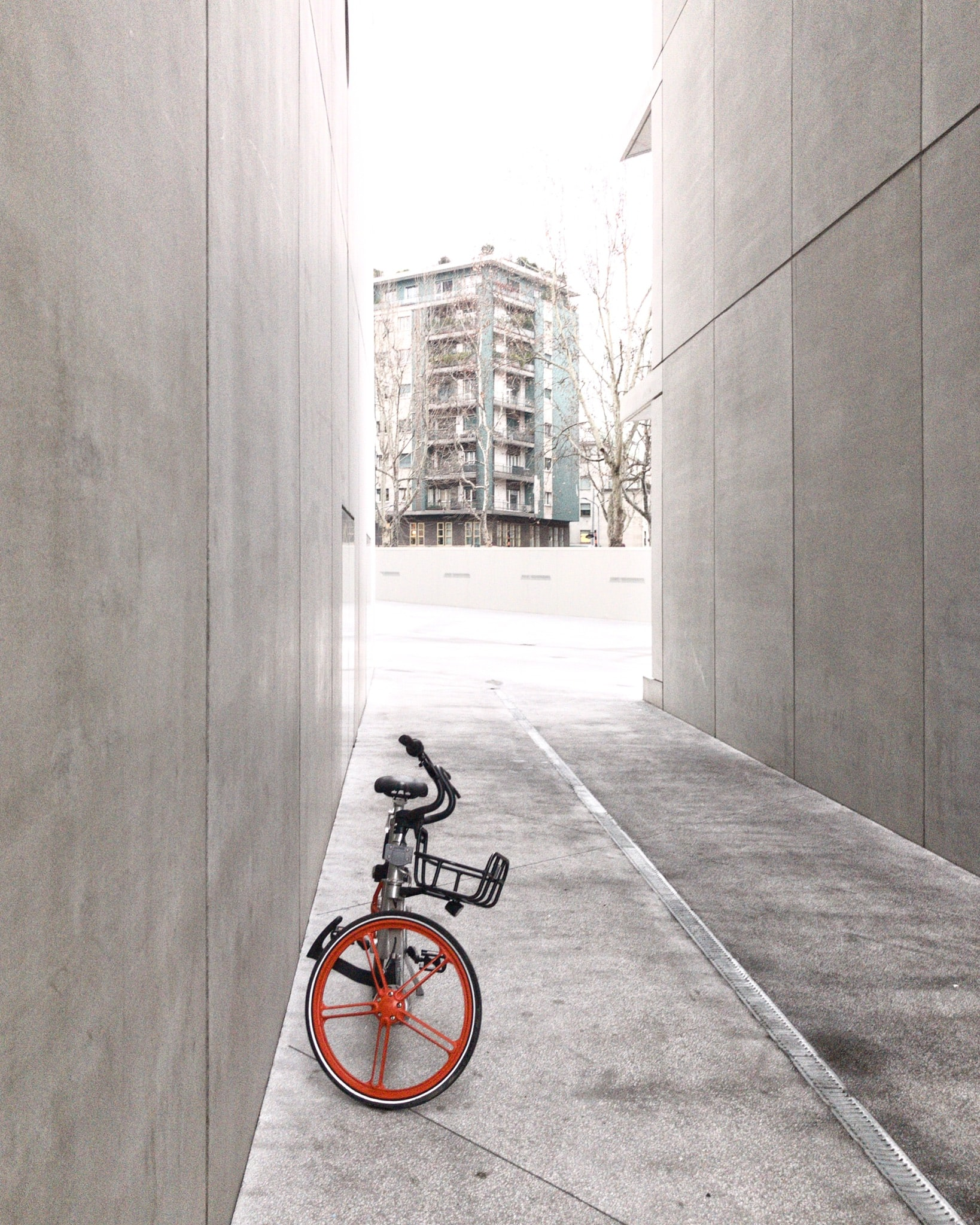 black and orange bicycle in between concrete walls