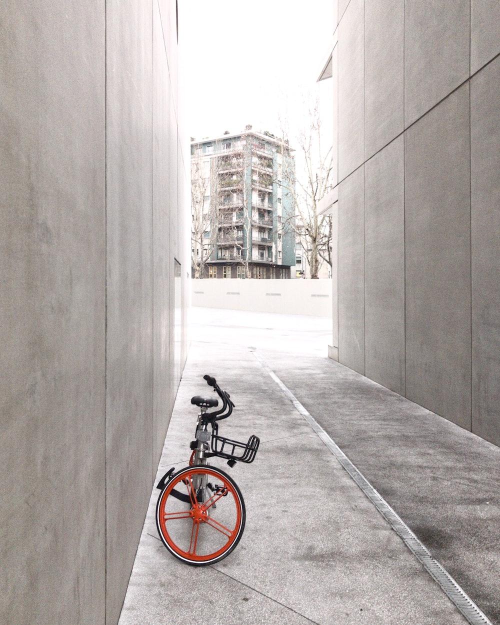black and orange bicycle in between concrete walls