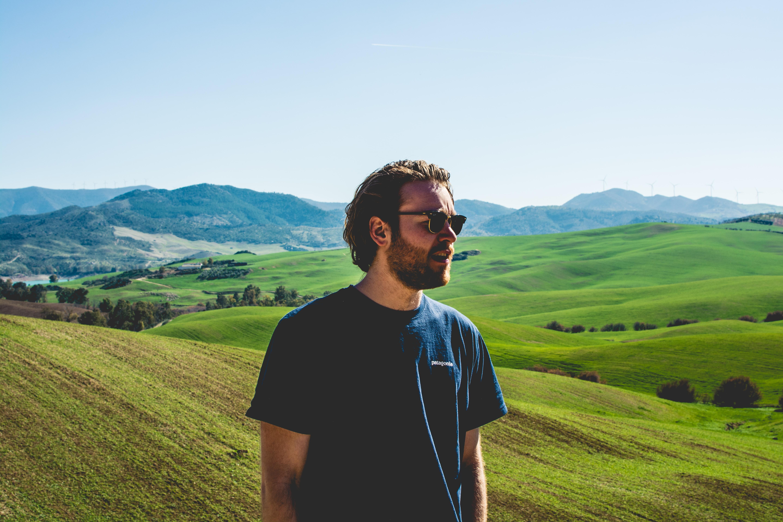 man wearing black crew-neck t-shirt standing near hill at daytime