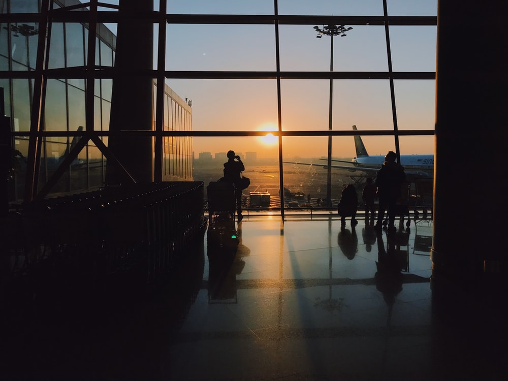 silhouette of people standing inside airport during golden hour