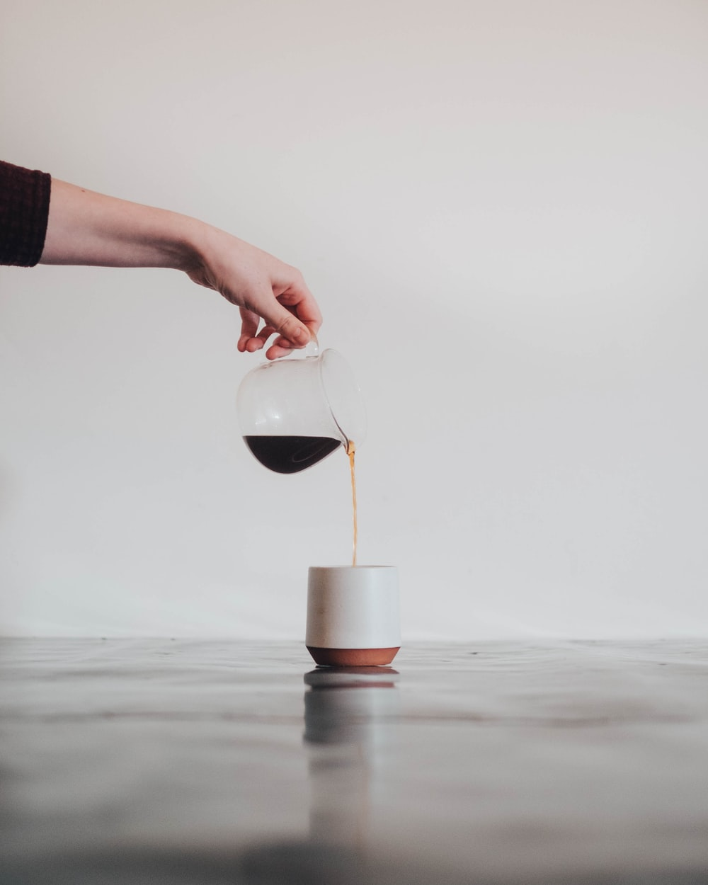person pouring coffee in white mug