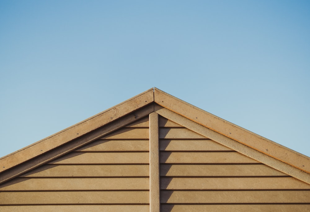 photo of brown wooden house roof under clear blue sky