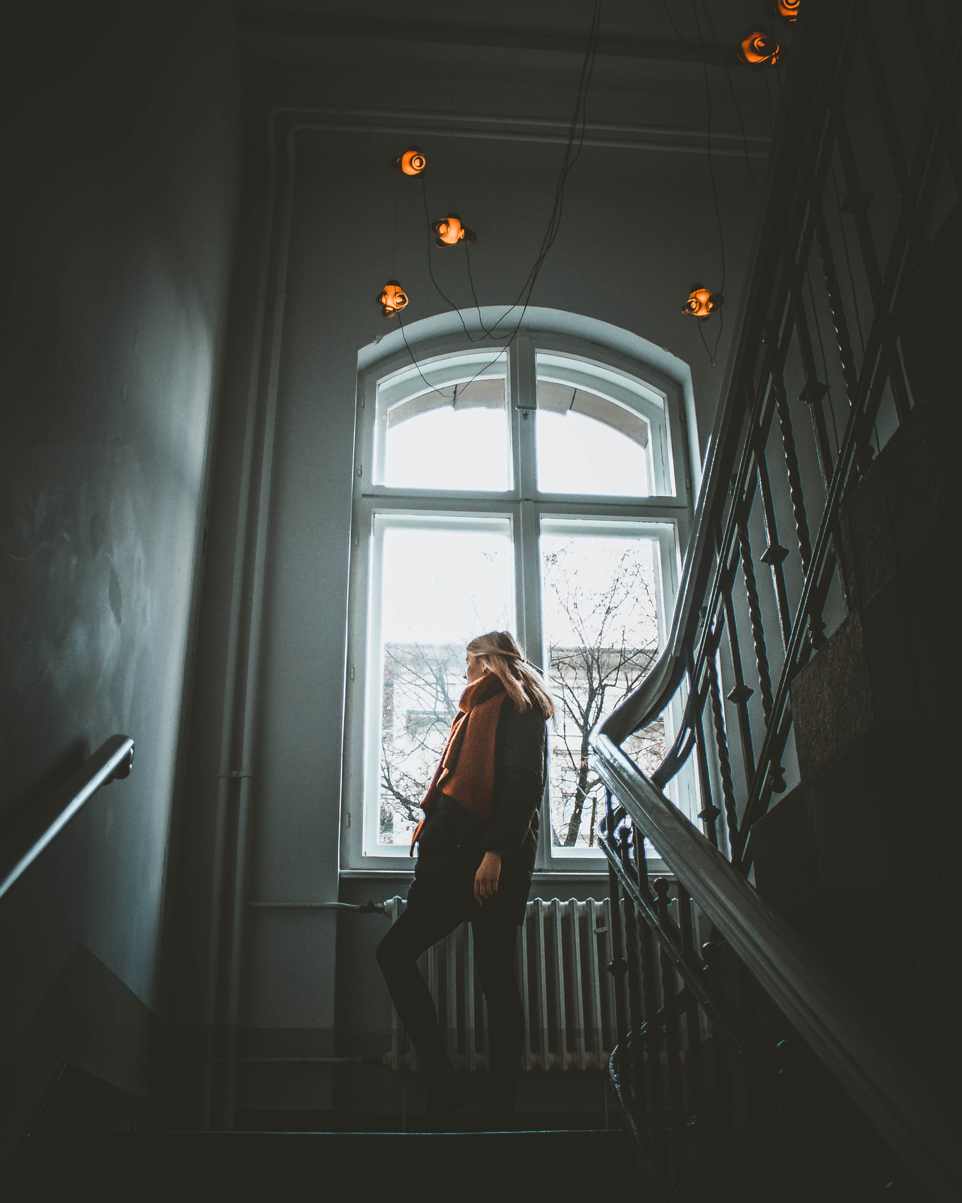 woman standing on stair looking at window at daytime