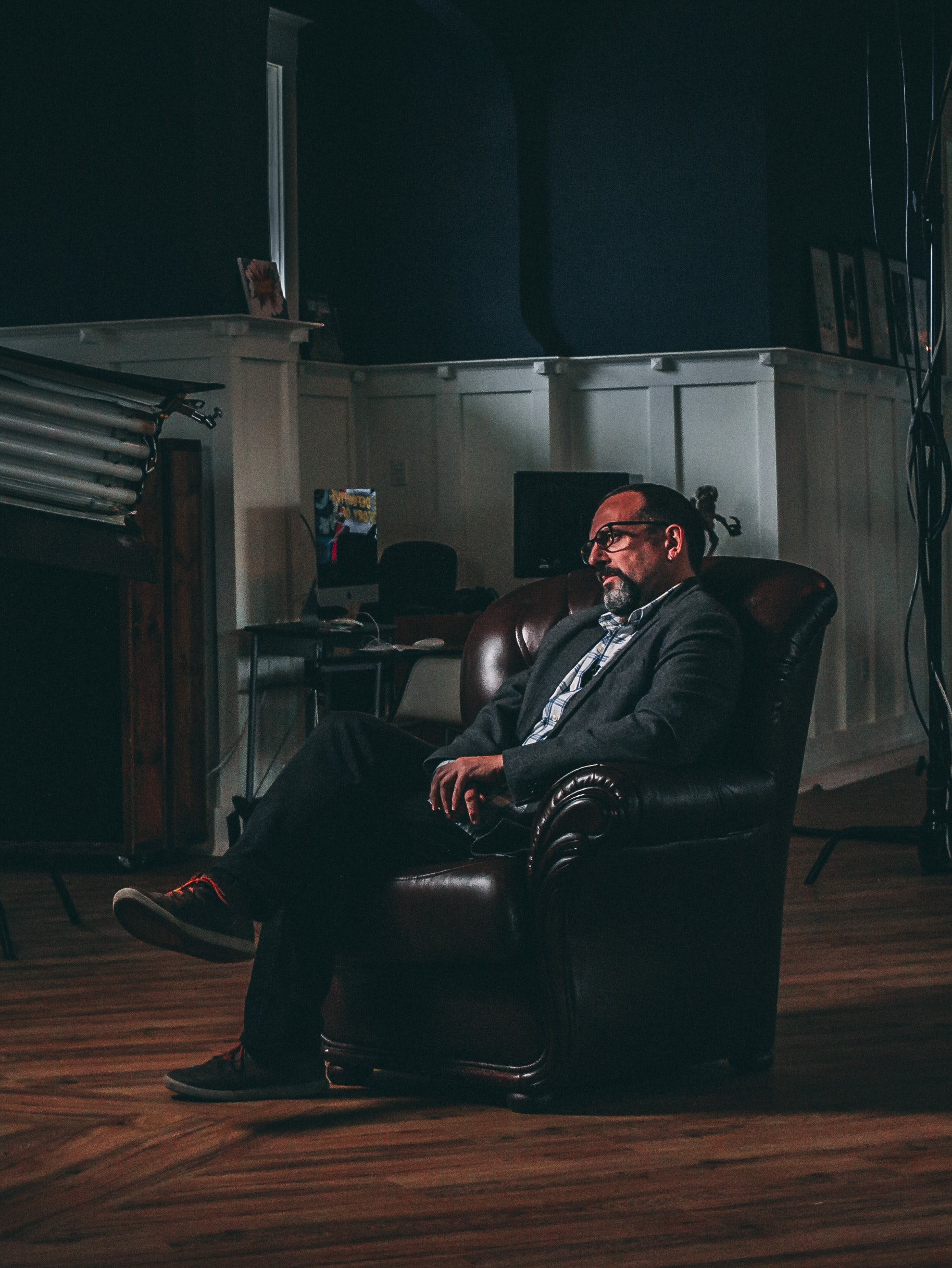 man sitting on brown leather sofa chair near brown wooden cabinet
