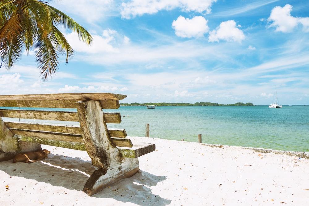brown wooden bench on white beach sand