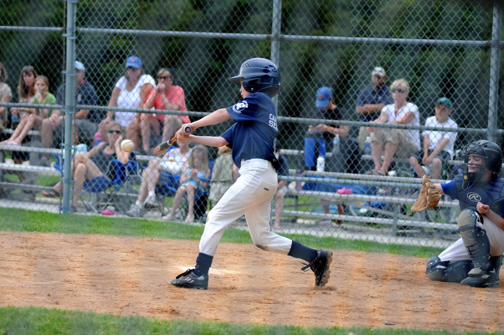 boy batting baseball near catcher beside gray fence