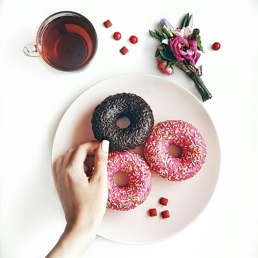 person holding black donuts