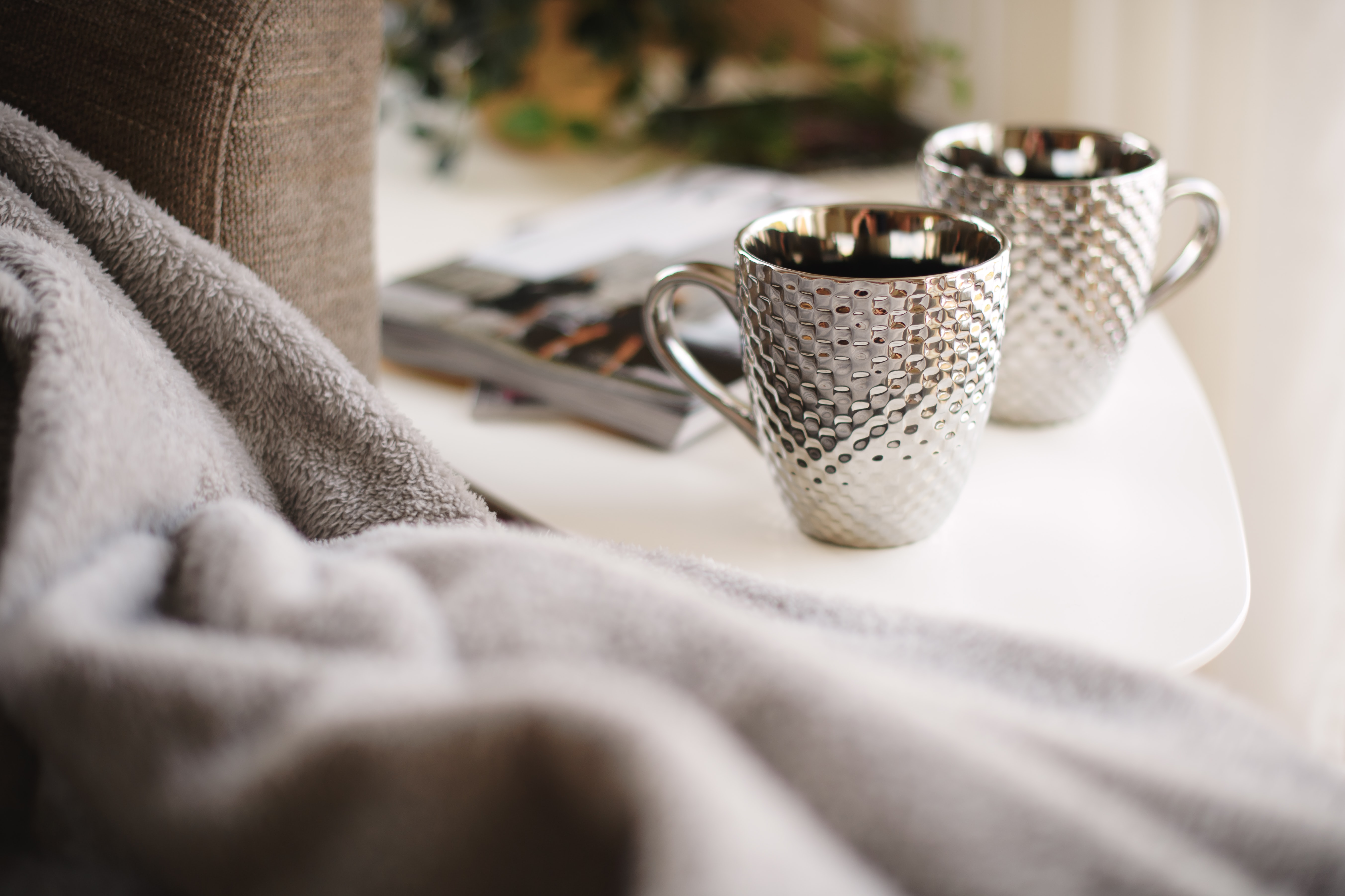 two silver mugs on white side table