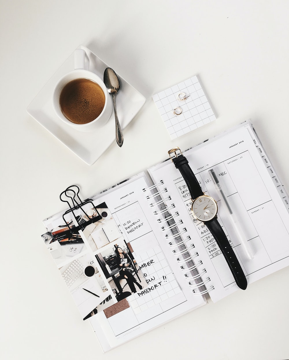 analog watch on top of book beside white ceramic teacup with teaspoon