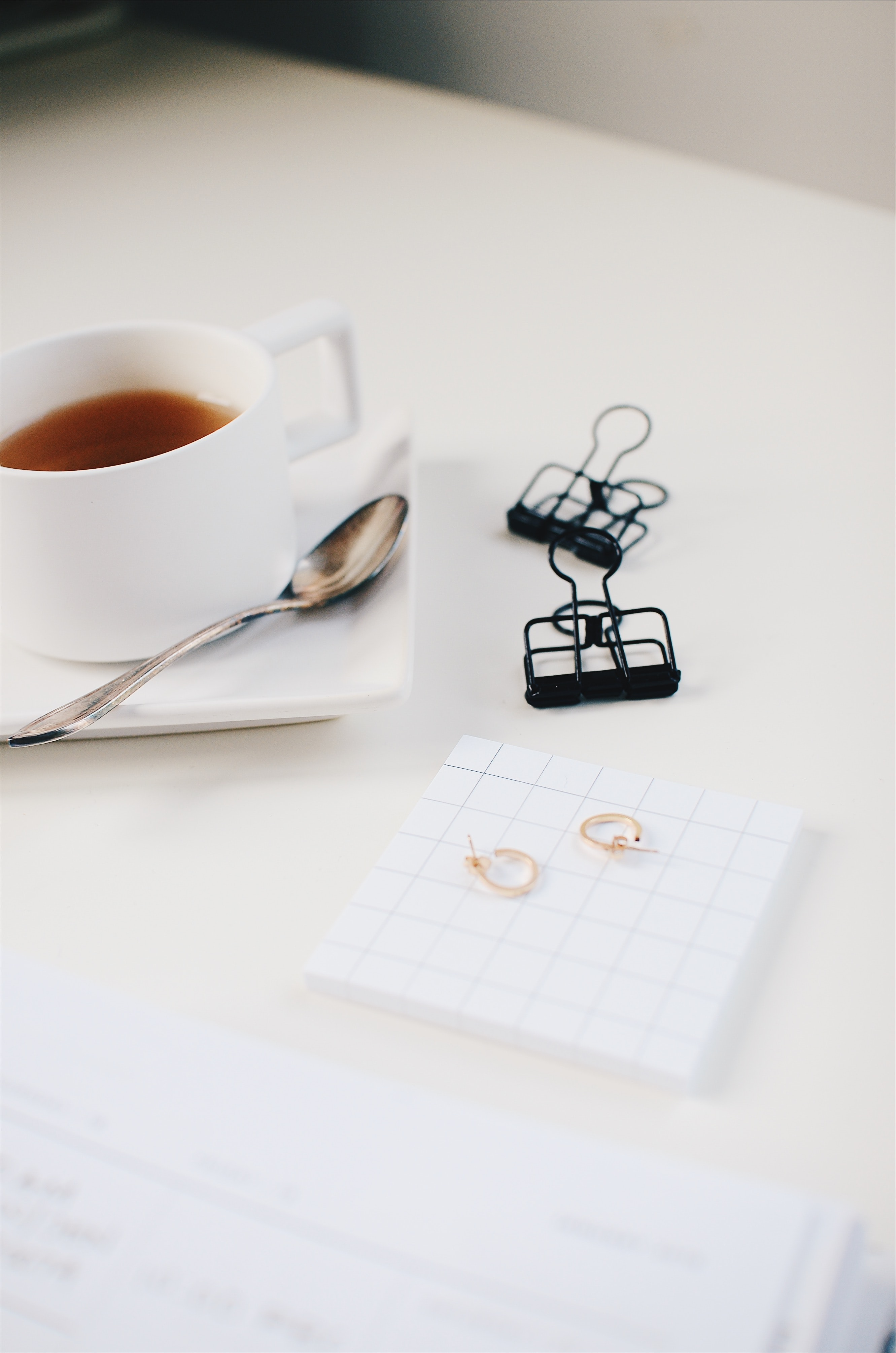 cup of tea with two black paper clips