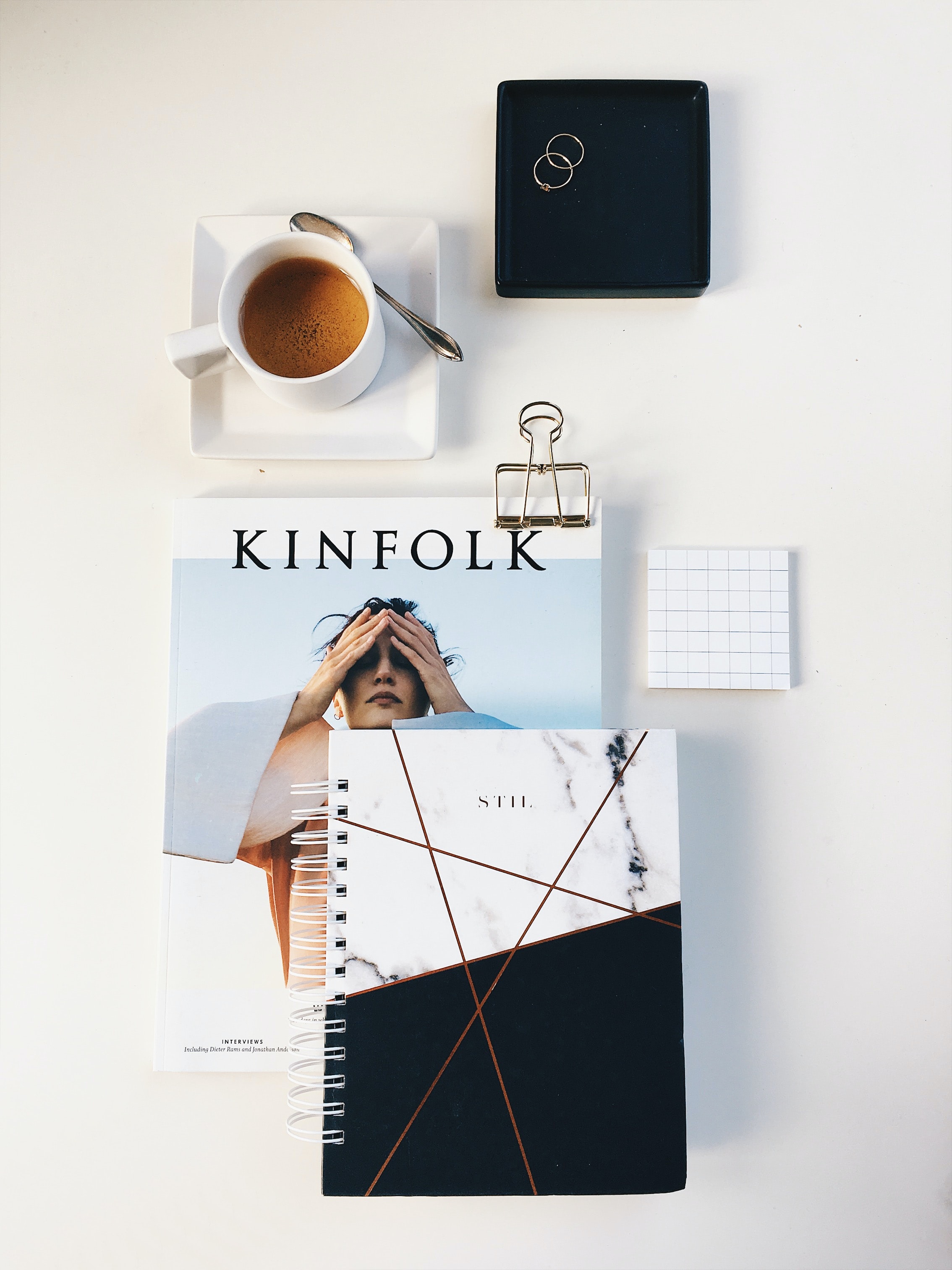 flat lay photography of cup, rings, and notebook