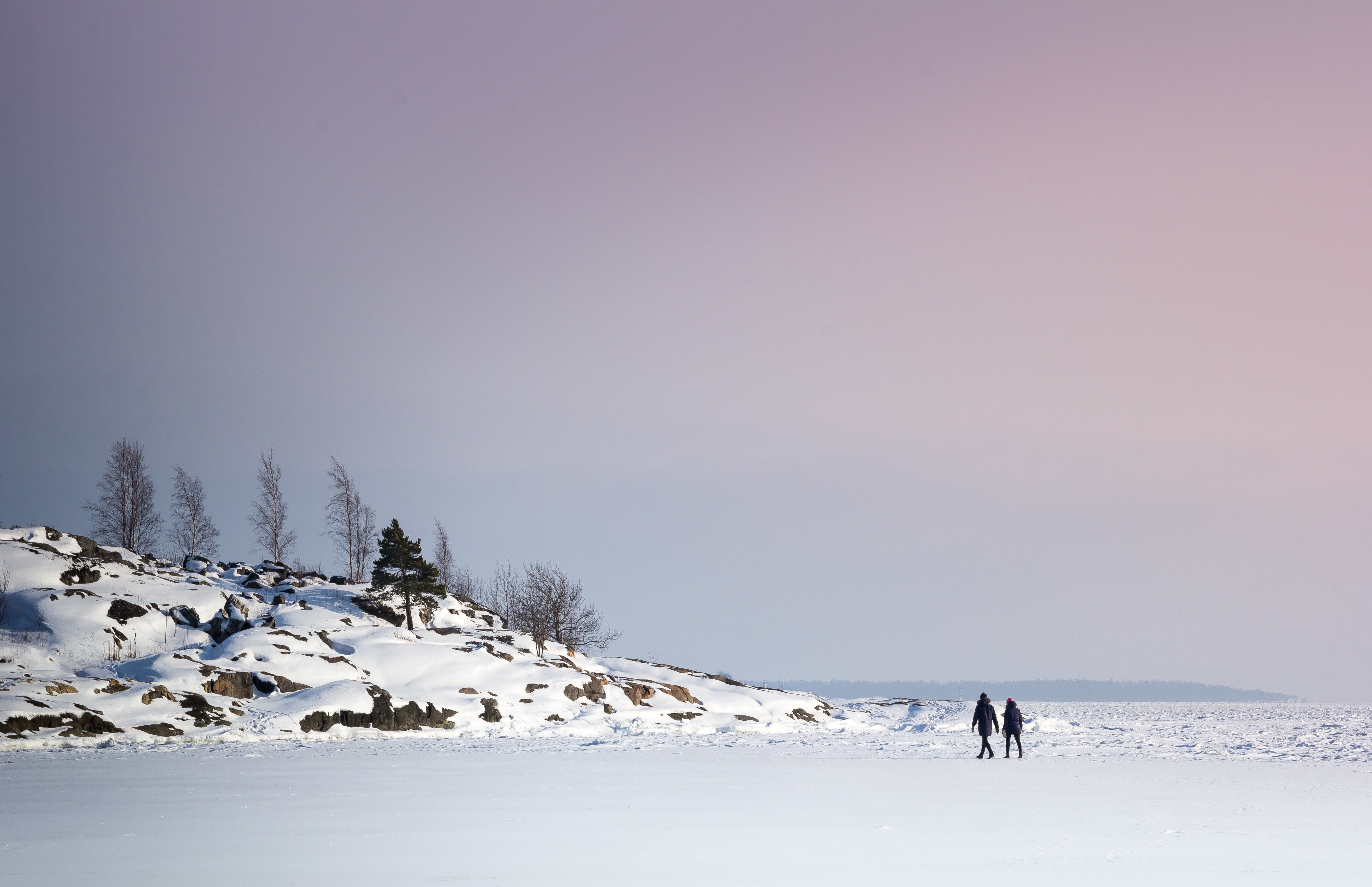 two person walking on lake with ice