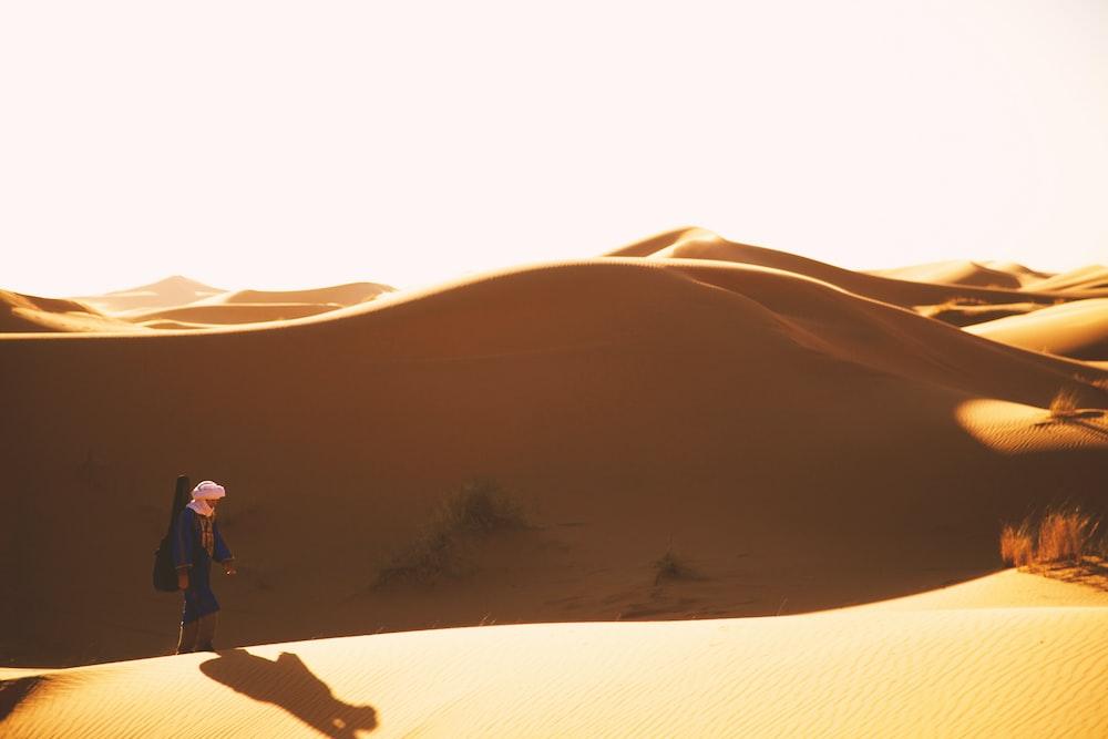 man walking on desert at daytime