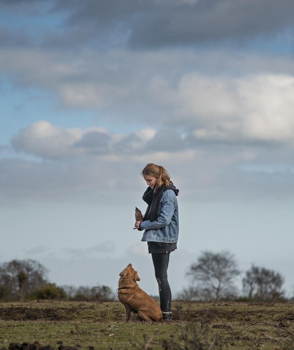 woman in blue denim jacket standing beside short-coated brown dog
